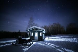 Snowmobile in front of Cabin under stars in Hudson Bay Saskatchewan