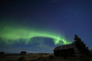Aurora band in sky over farmyard